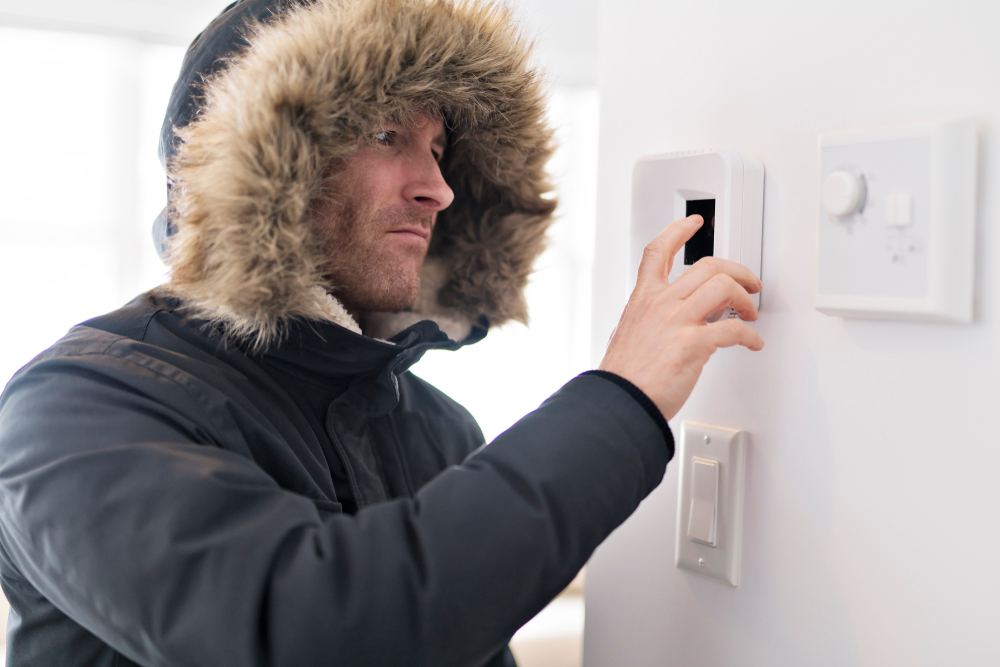 Man adjusting thermostat in a cold house