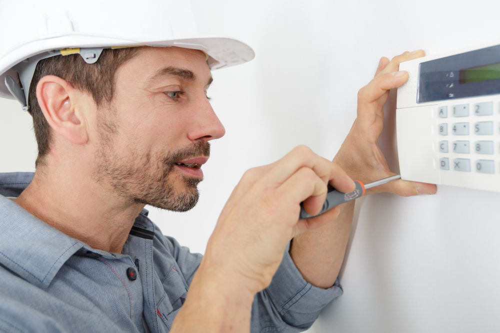 heating technician working on a thermostat